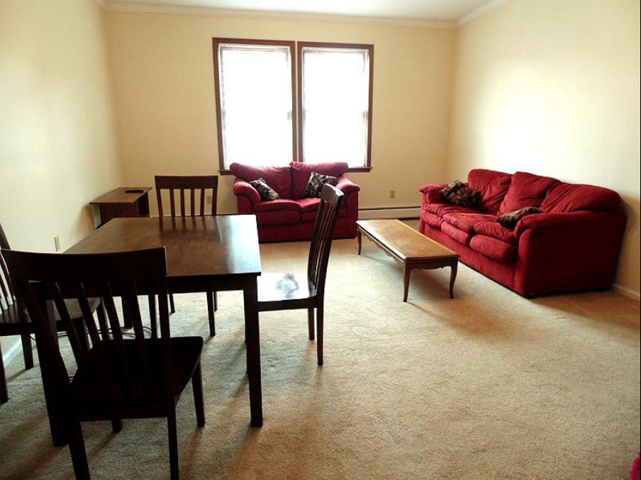 student apartments near suny cortland image of fully furnished living room with two couches coffee table 4 chairs and dining table from sap properties
